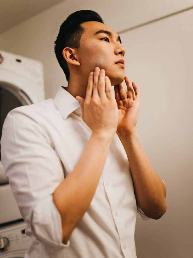 Man putting lotion on his face.