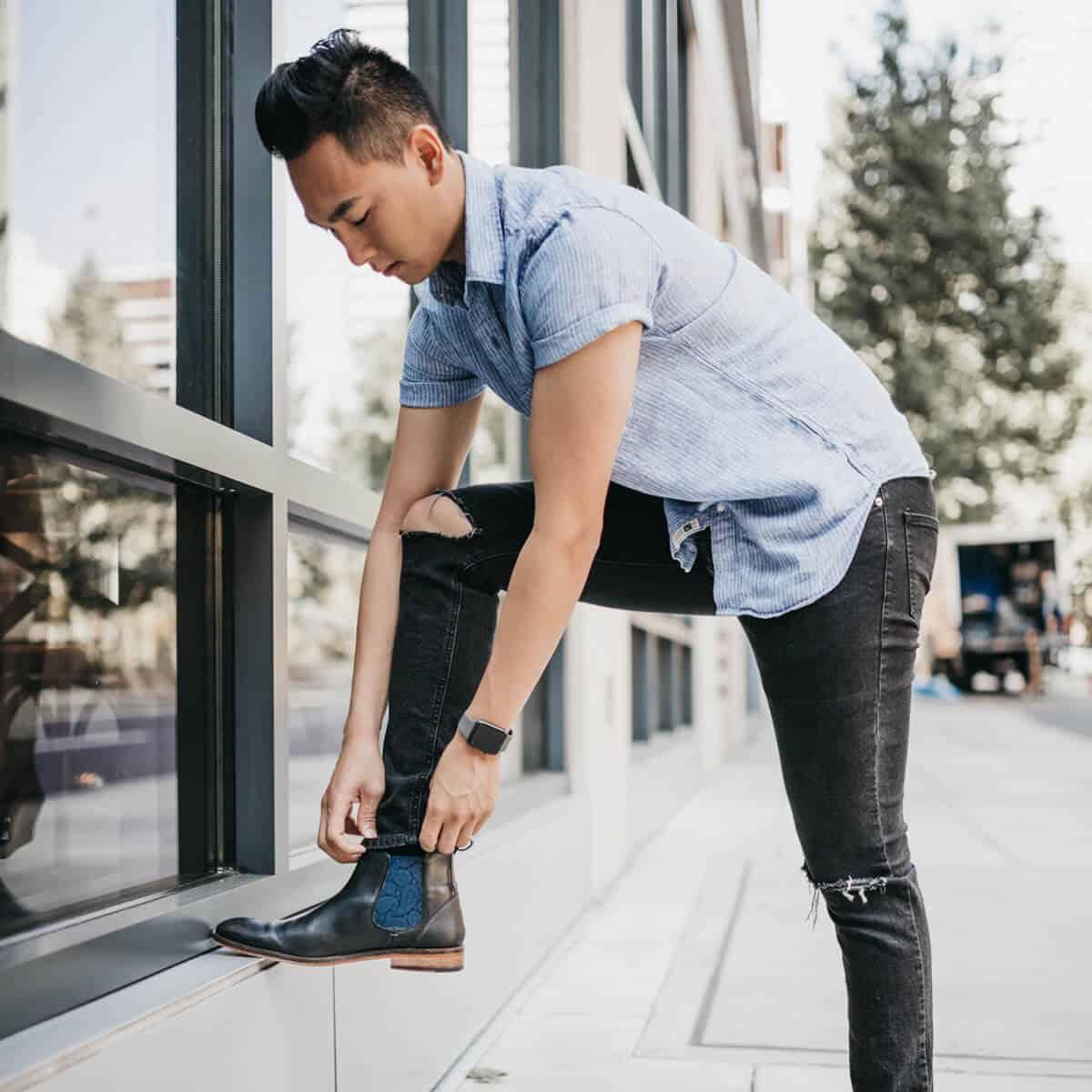 Man rolling his pants with his foot on a ledge.
