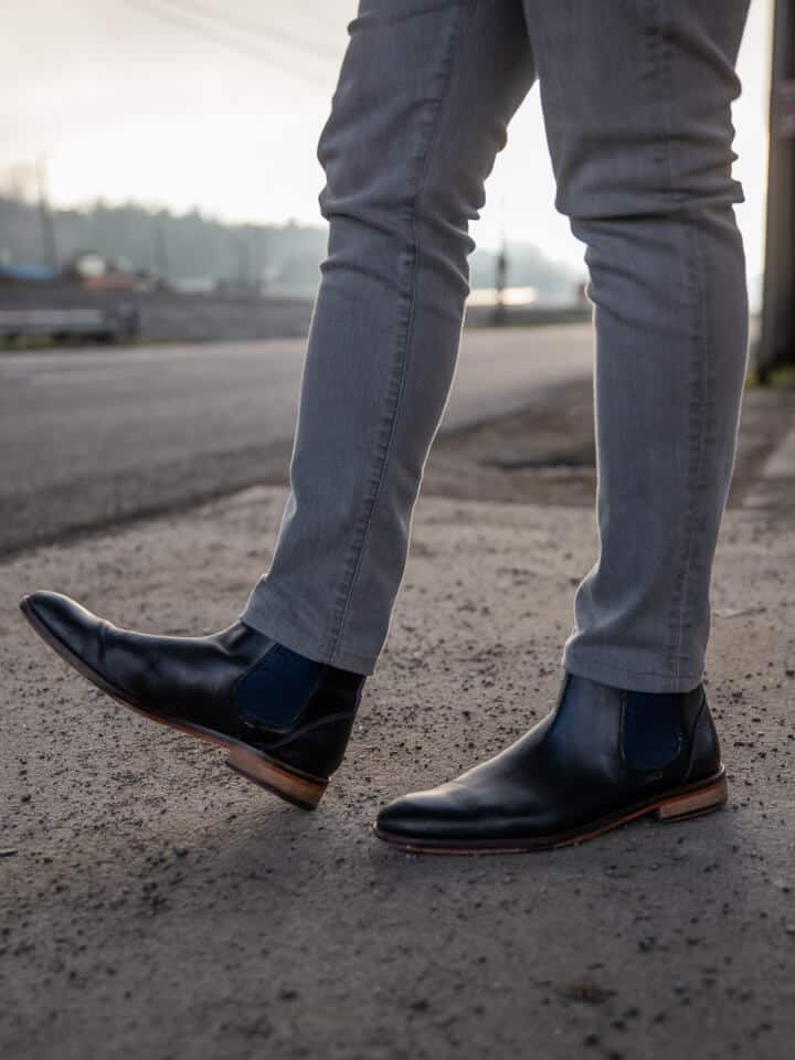 Black leather Chelsea boots with grey jeans.