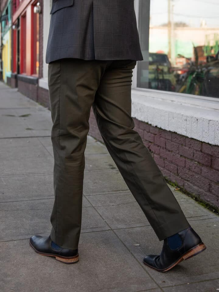 Lower half of the body with Olive Green pants and black leather Chelsea boots.
