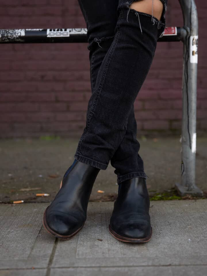 Legs crossed with black jeans and black leather Chelsea boots.