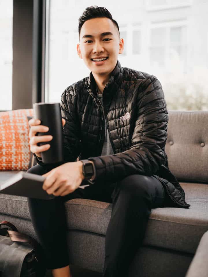 Man sitting down, holding a black mug, and smiling.