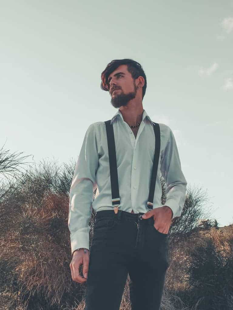 A man wearing suspenders with one hand in his pocket.