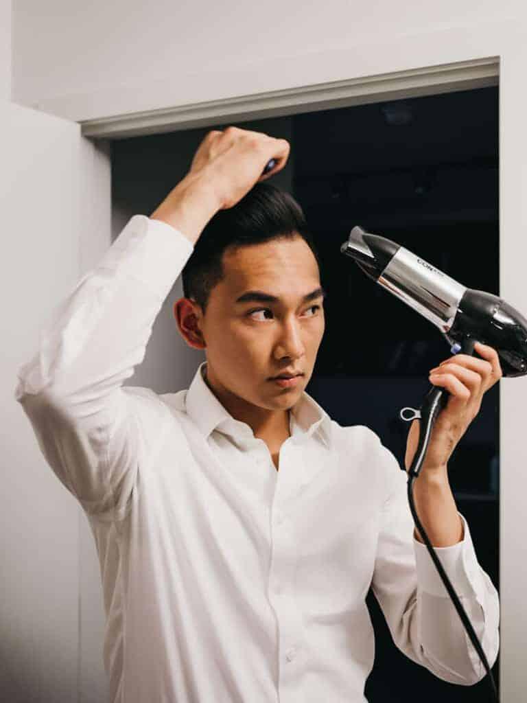 A man blow drying his hair.