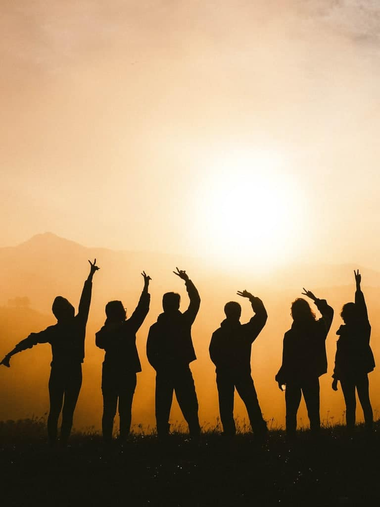 Silhouette of a group with their hands up.