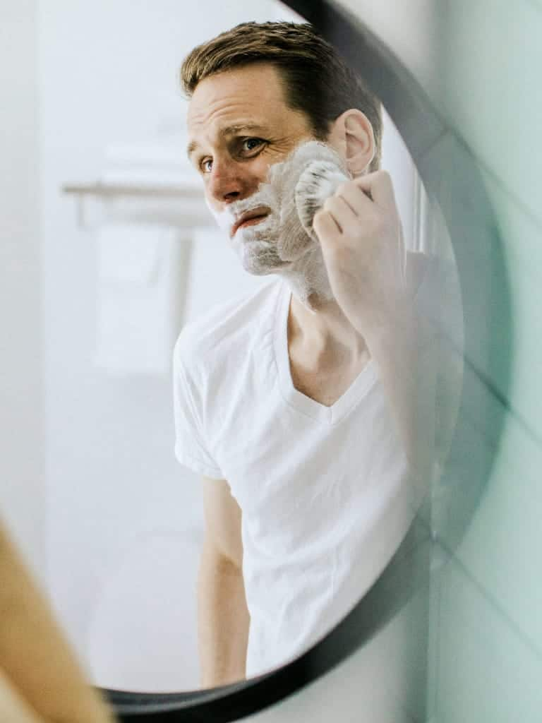A man brushing his face.