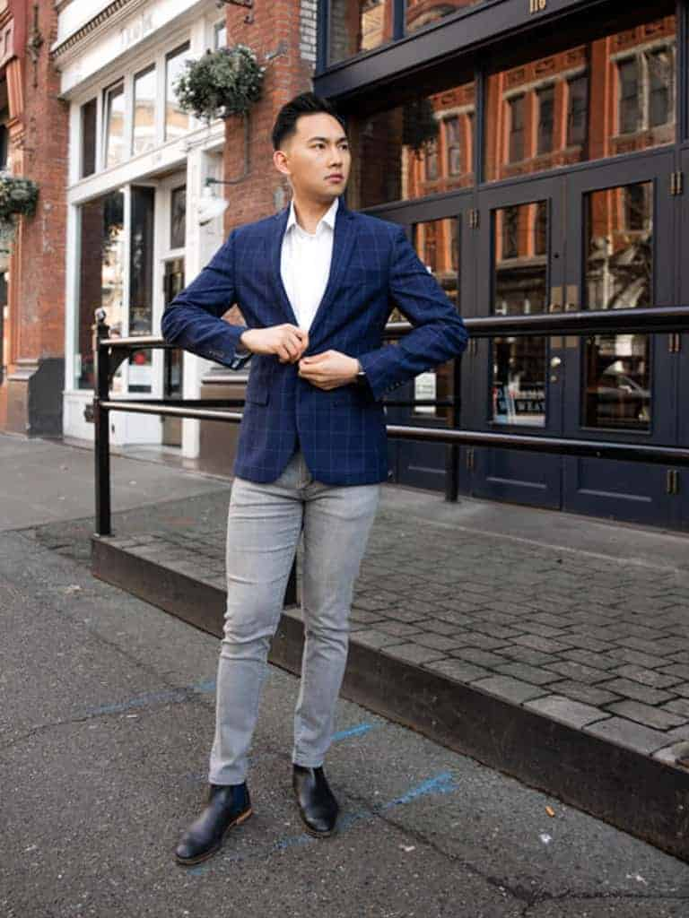 A man with a blue sport coat and grey jeans.