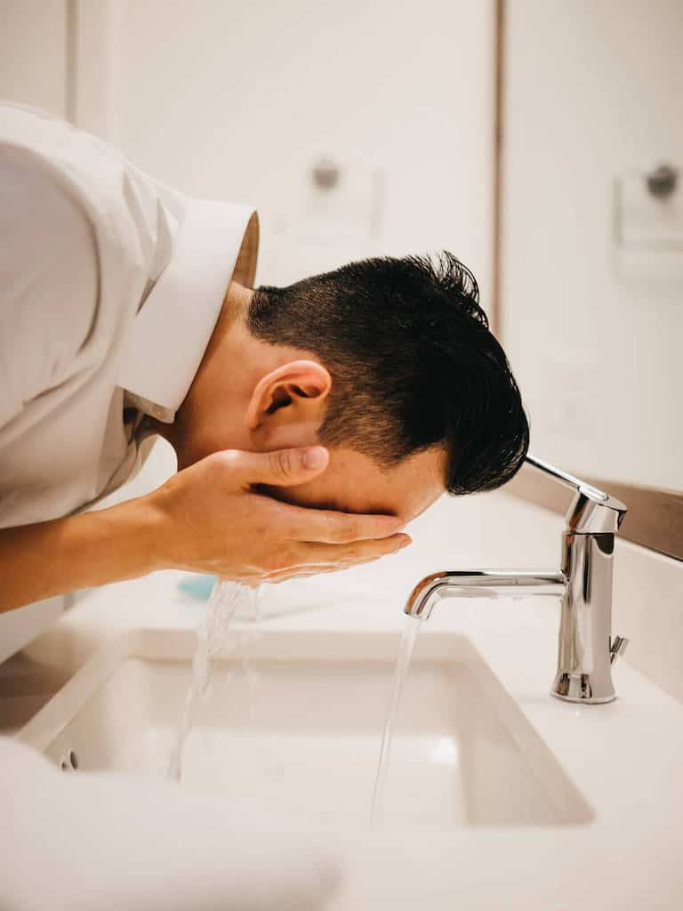 Person washing face in the sink.