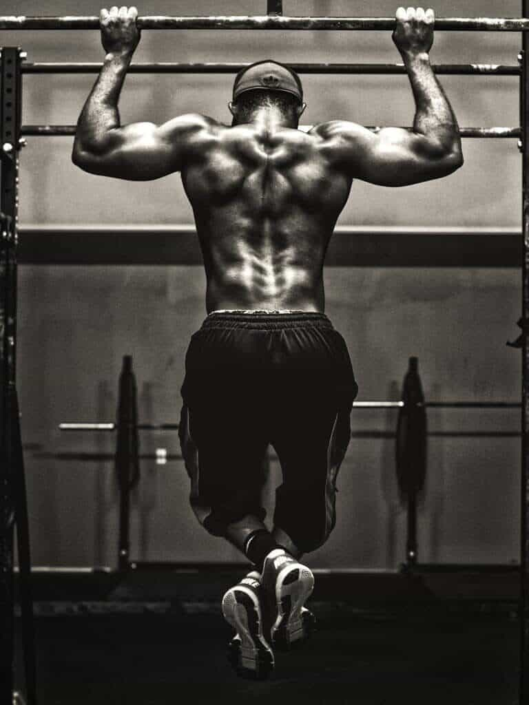 Grayscale image of a man doing a pull-up.