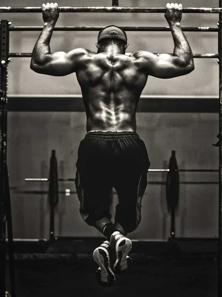 A grayscale image of a man doing a pull-up.