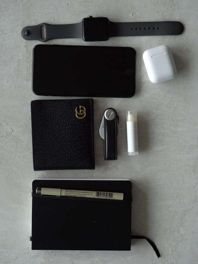 Flatlay of a watch, phone, AirPods, wallet, key organizer, lip balm, notebook, and a pen.