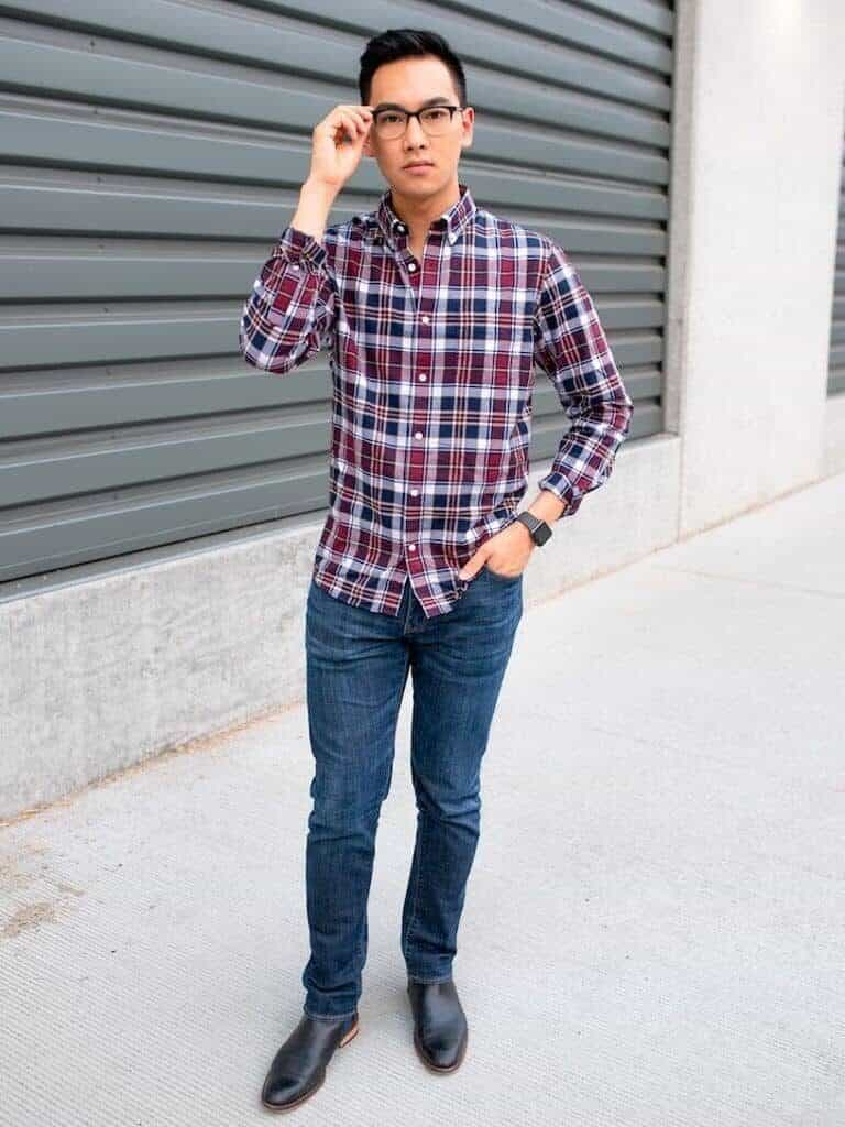 A man wearing a plaid shirt with blue jeans.