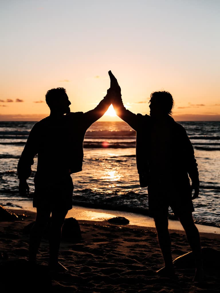 Silhouette of two men giving each other a high-five.