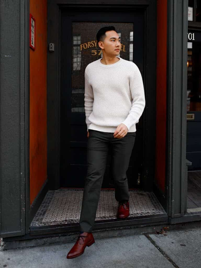 Person stepping out of a building and looking to the side.