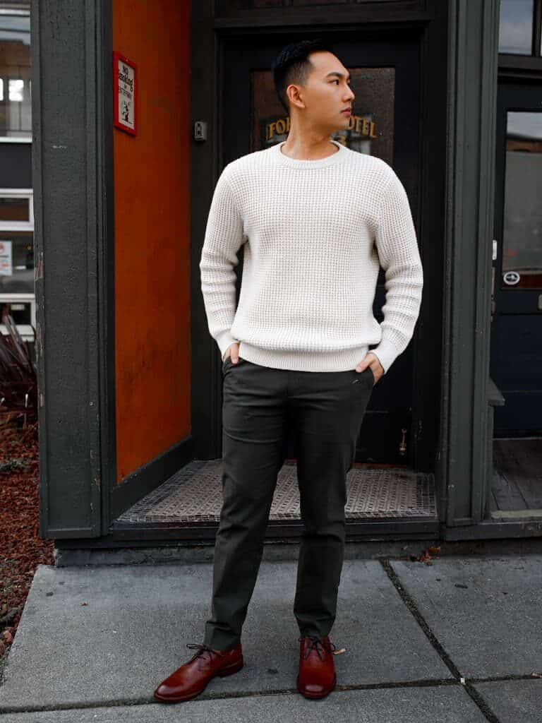 Person standing in front of a door with their hands in their pocket.