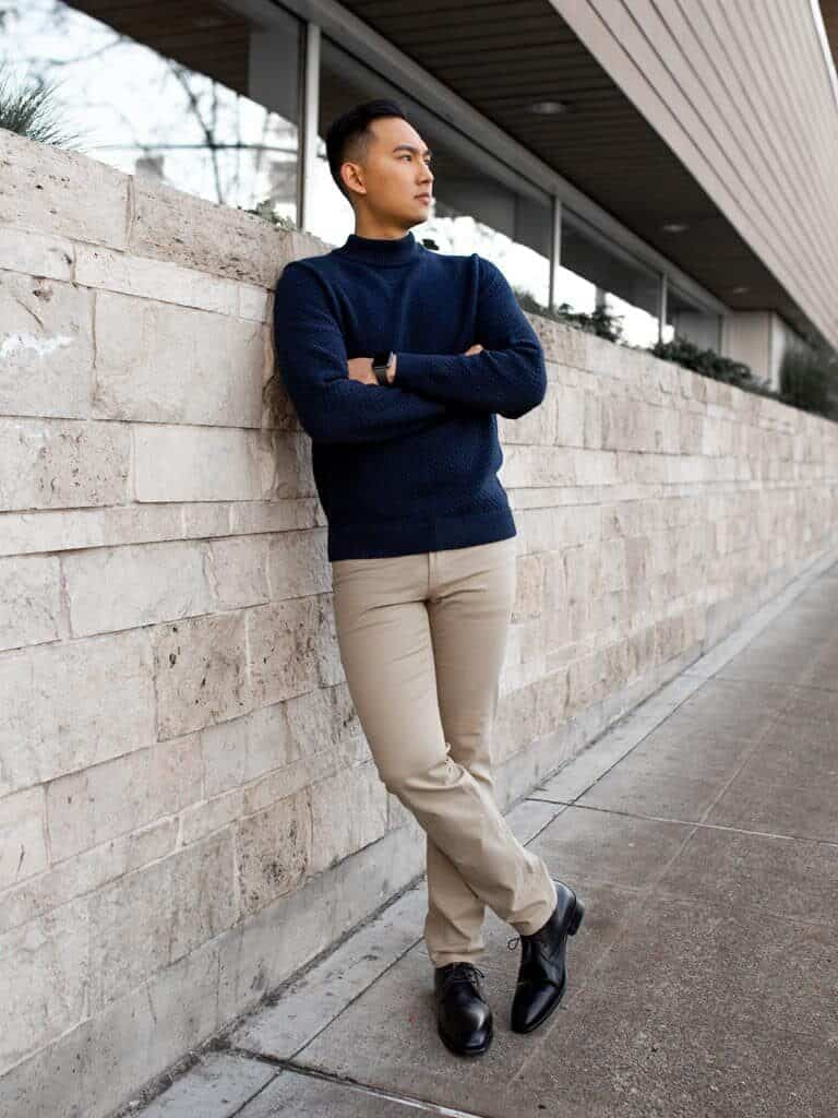 Person leaning on a brick wall and looking to the side.