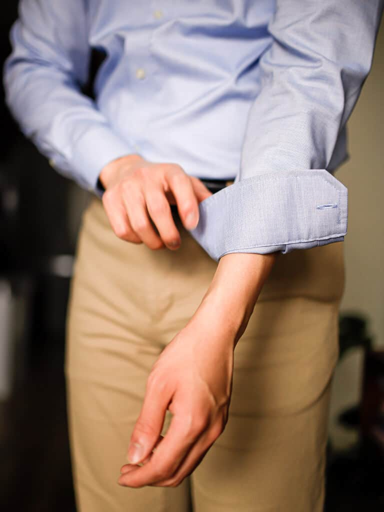 Person flipping cuff of shirt sleeve.