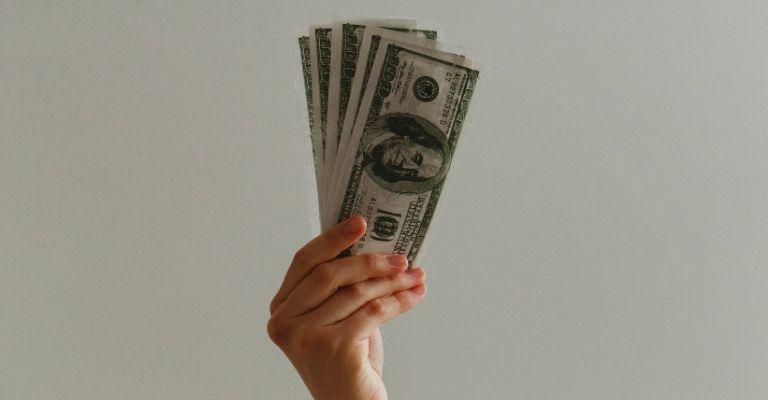 Hand holding cash.