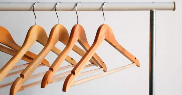 Wooden hangers on a bar.