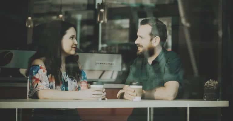 Two people talking in a coffee shop.