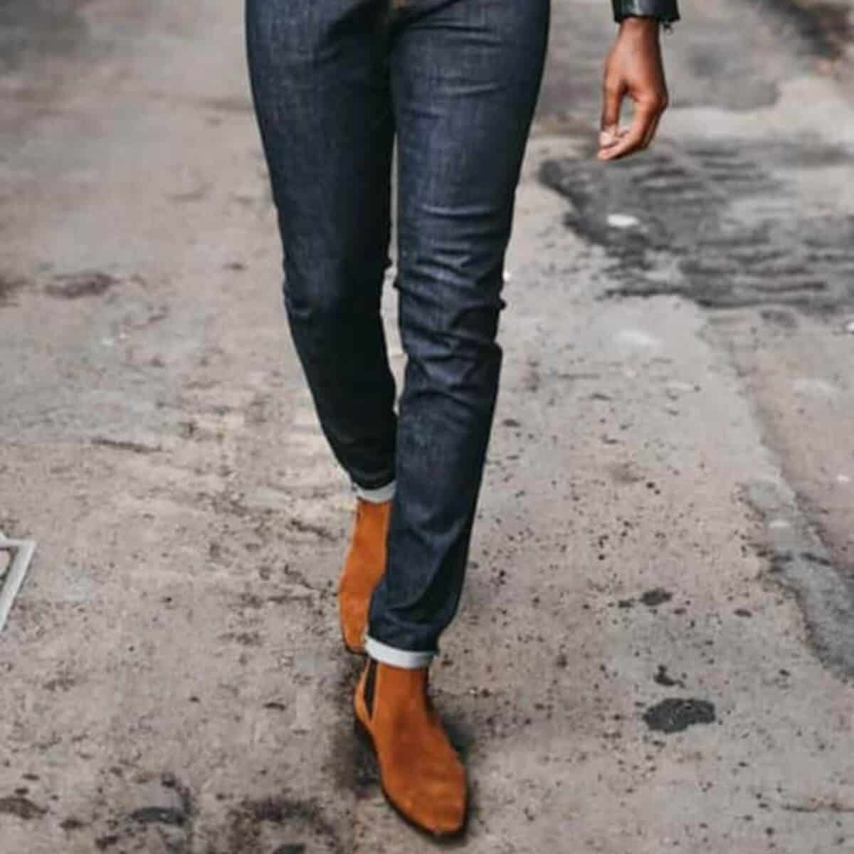 Lower half of a man wearing jeans and boots.