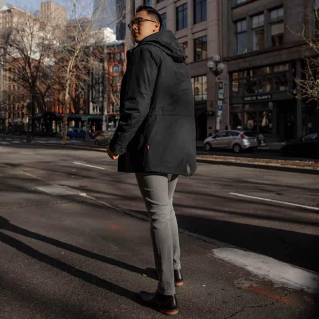 Man in grey jeans and rain coat walking.