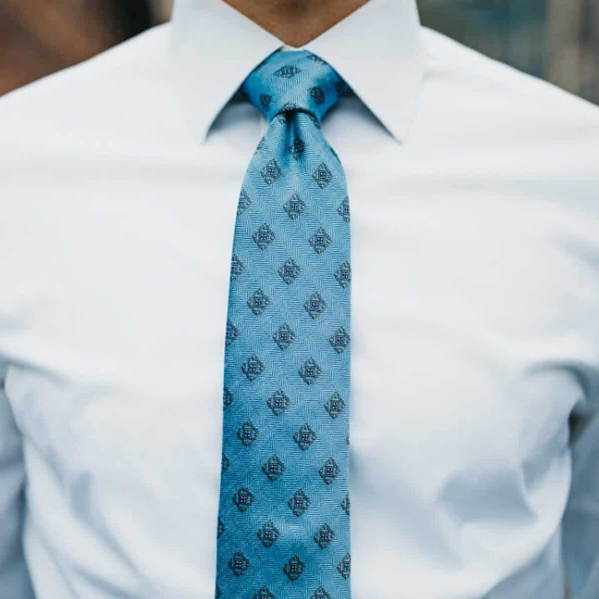 Close-up of a person's tie and white button-up shirt.