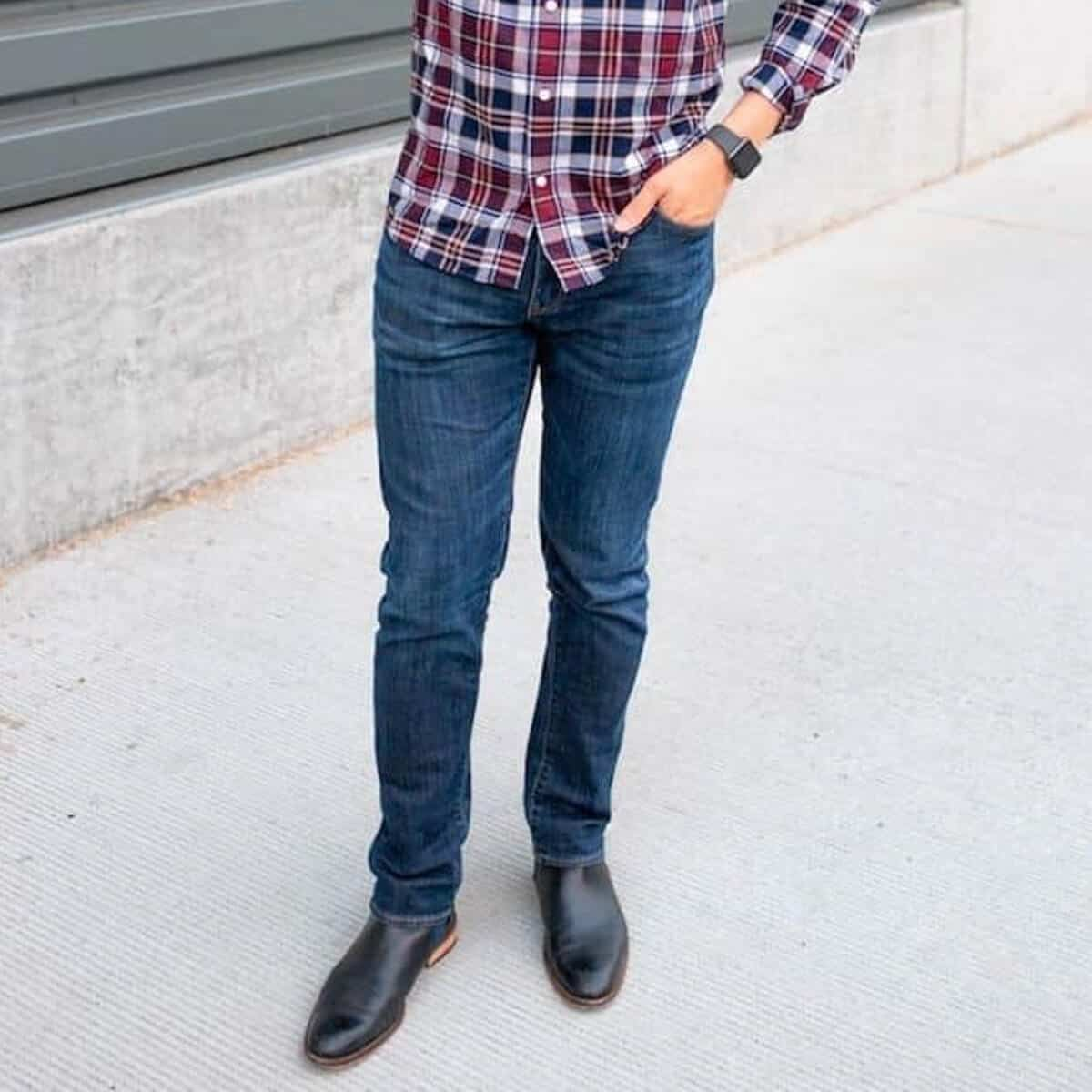 Person standing near a wall with a hand in their pocket.