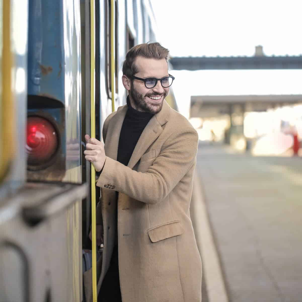Person stepping onto a train while looking back and smiling.