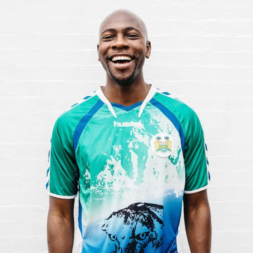 A smiling man wearing a soccer jersey.