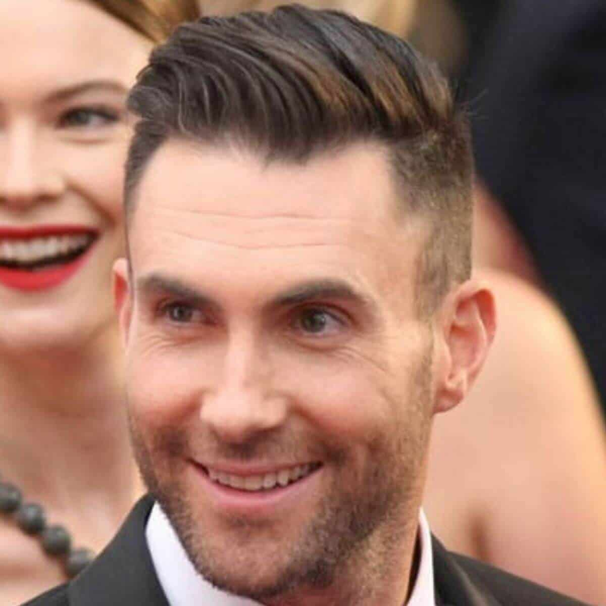 Headshot of Adam Levine wearing a suit.