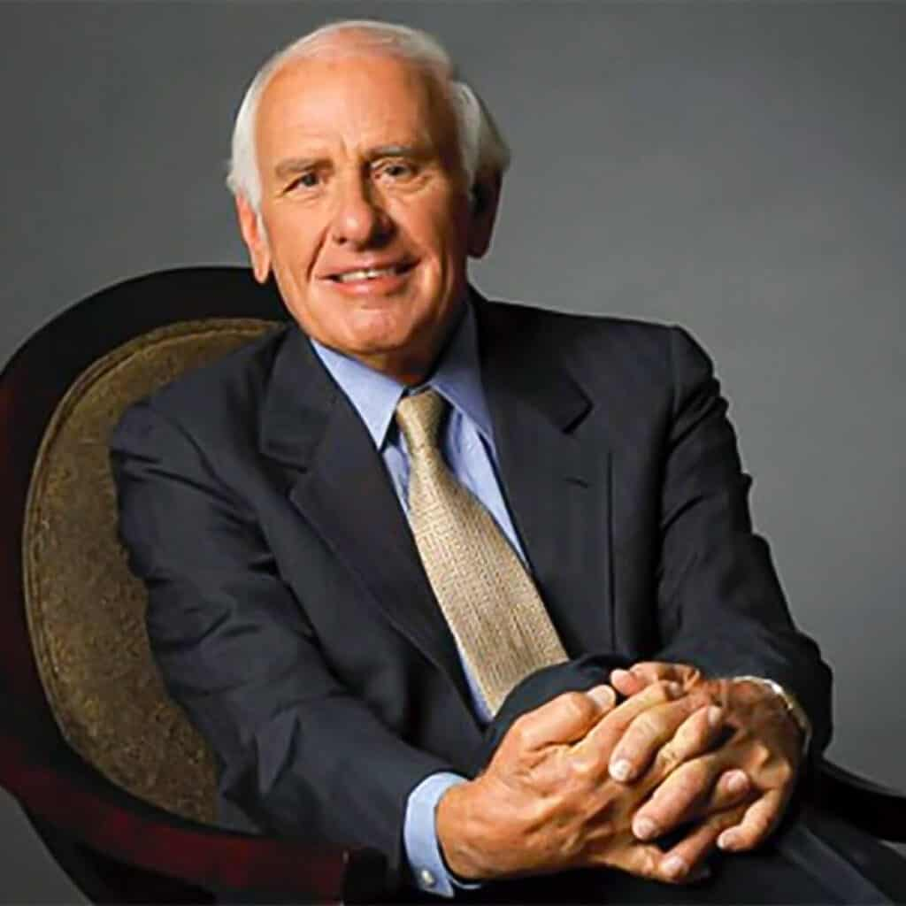 Jim Rohn sitting down with his hands together.
