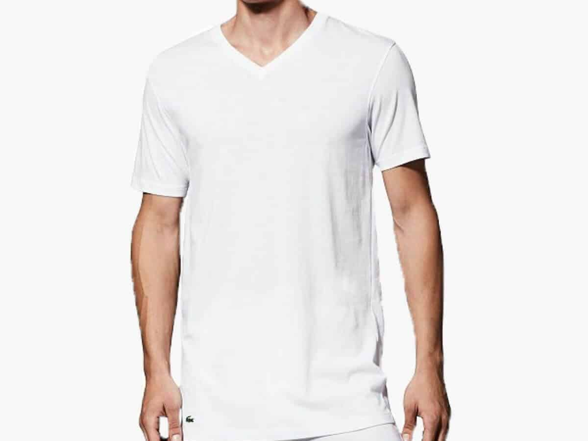 Person wearing a white Lacoste v-neck undershirt.