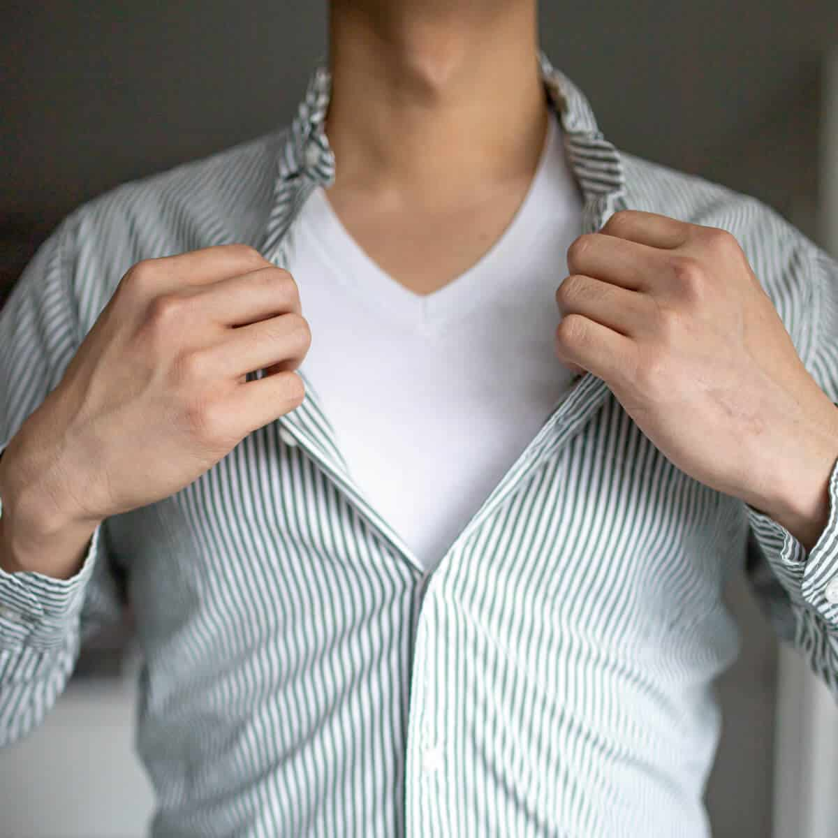 Person holding their shirt open to show their undershirt.