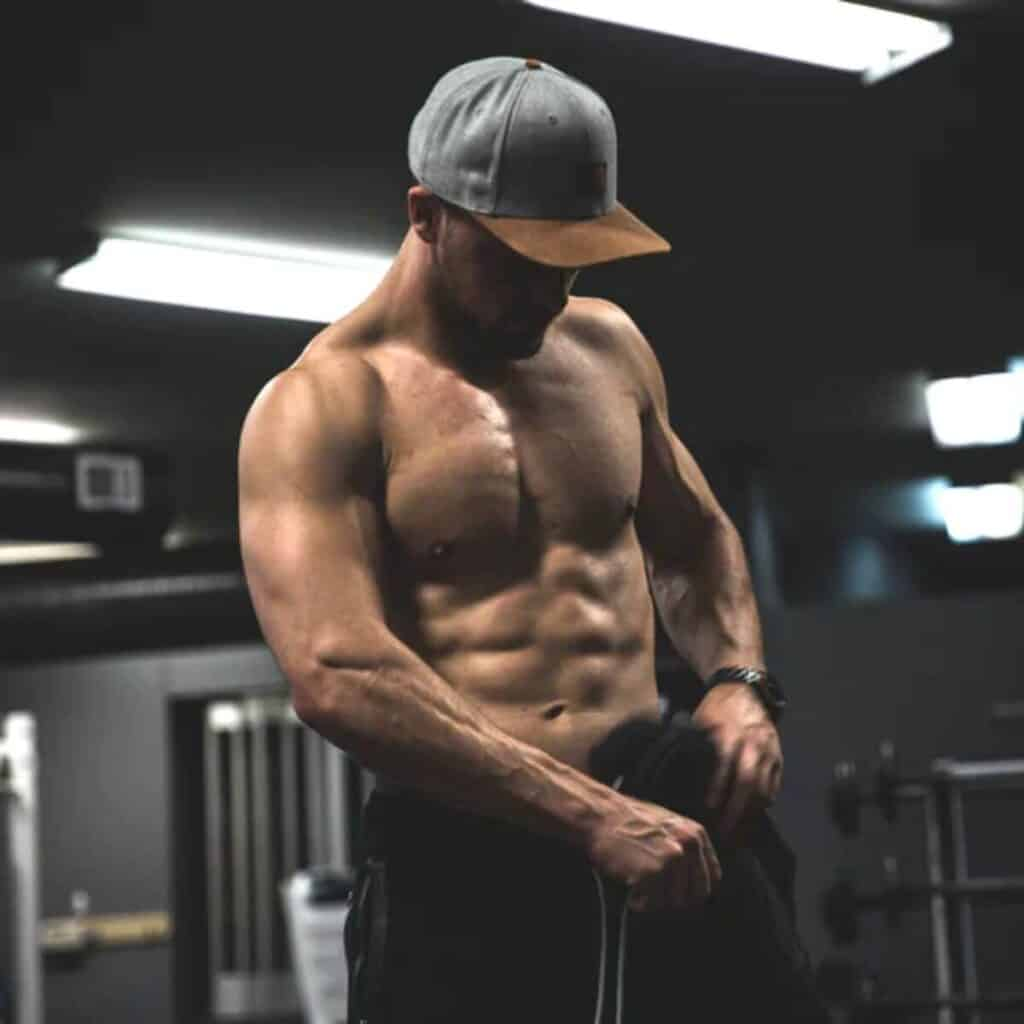 Shirtless person flexing muscles in a gym.