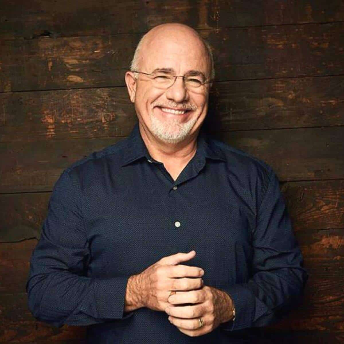 Dave Ramsey with a wooden background.