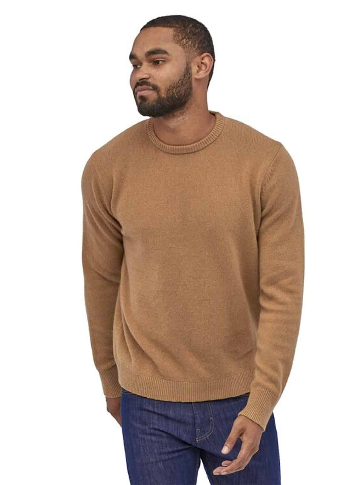 Person wearing a beige sweater and blue jeans.