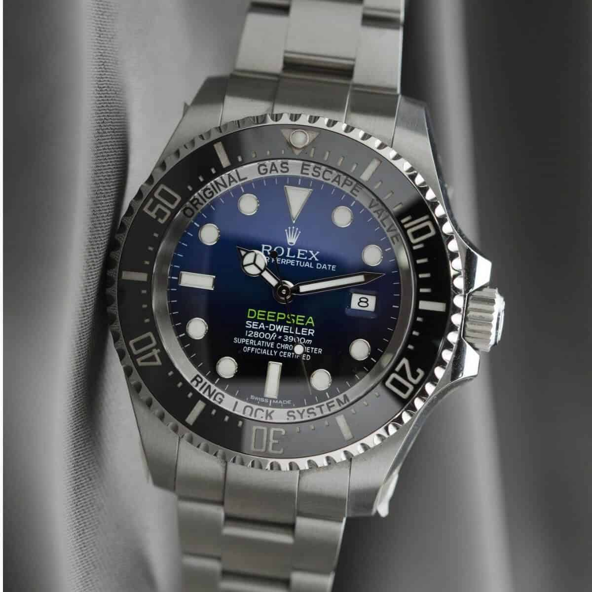 Rolex watch on grey cloth.