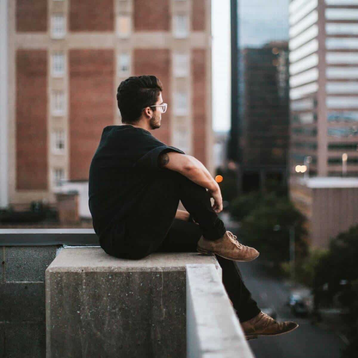 Person sitting on the edge of a building.