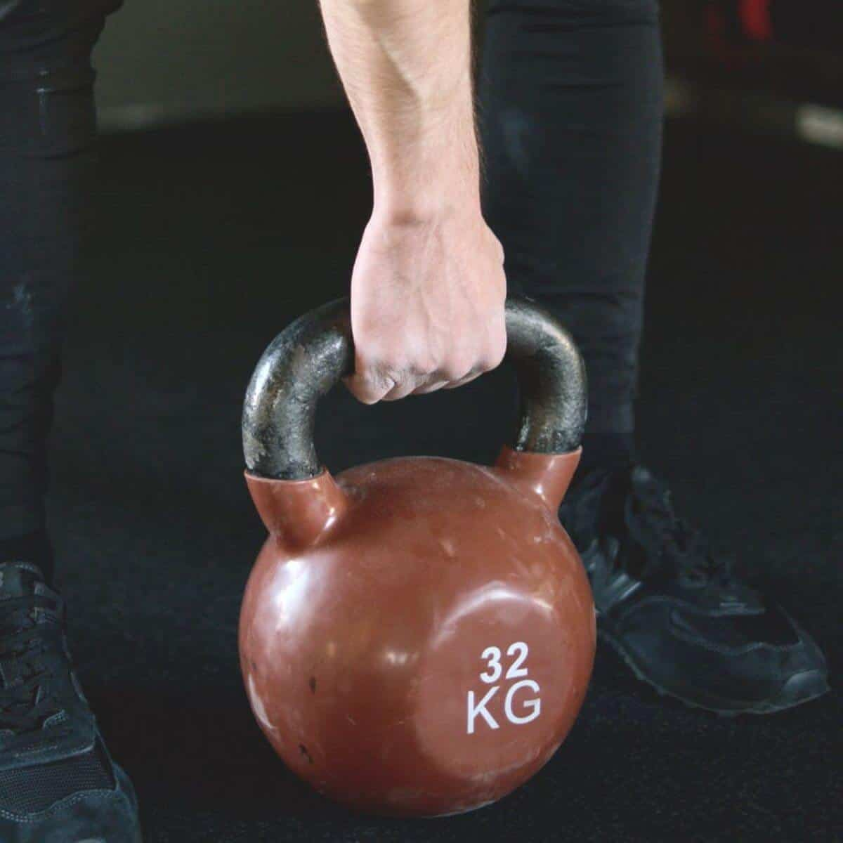 person holding a red kettlebell.