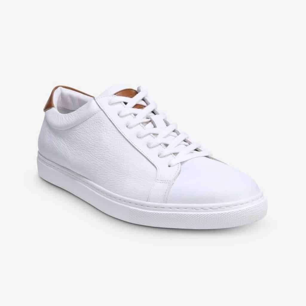 White leather dress sneaker with a piece of tan leather at the ankle.
