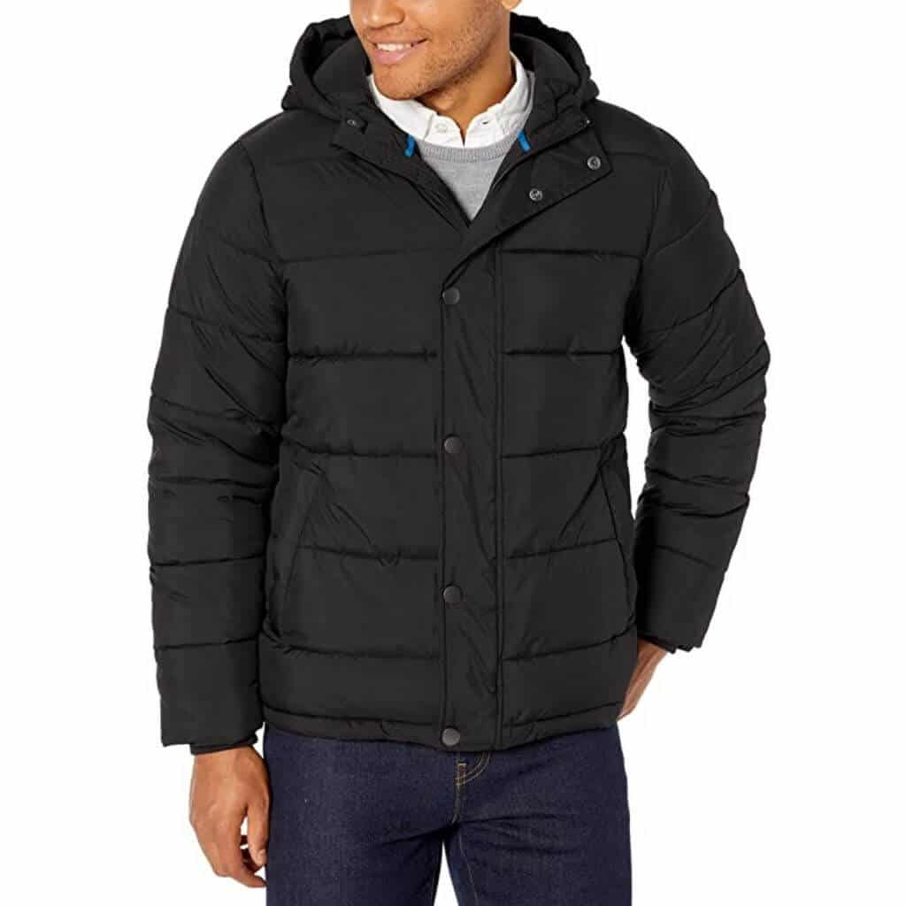 Person wearing dark blue jeans and a black puffer coat.