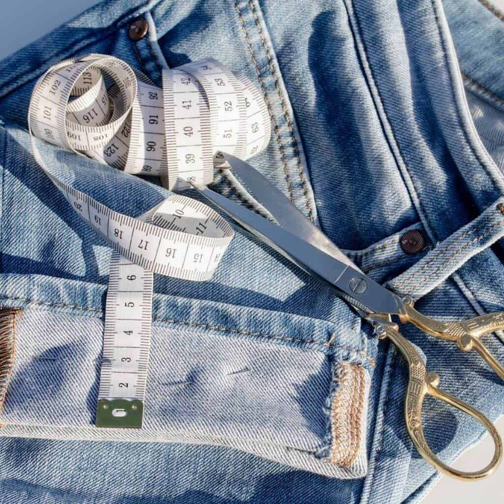 Tape measure and scissors on a pair of jeans with the cuff rolled.