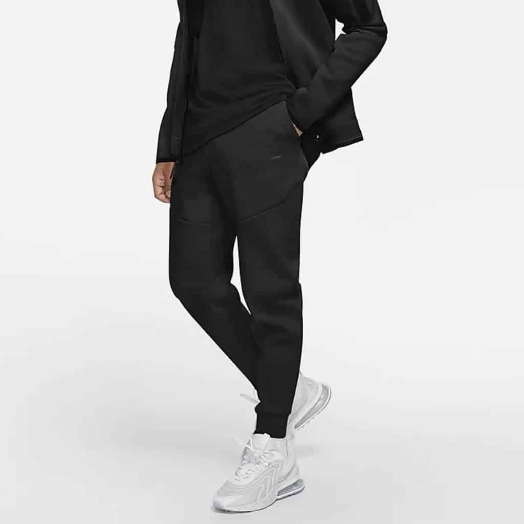 Lower half of a person wearing black Nike joggers.