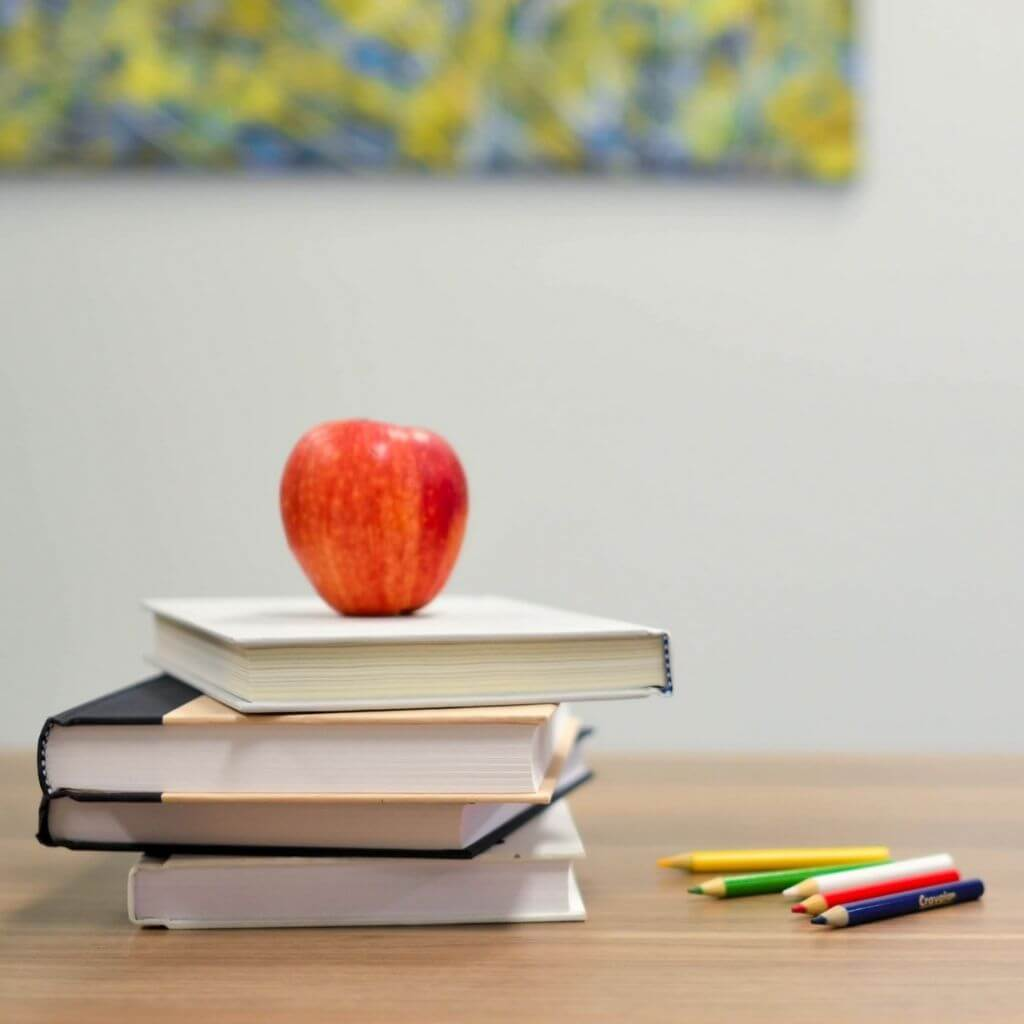 An apple on a stack of four books with colored pencils next to it.