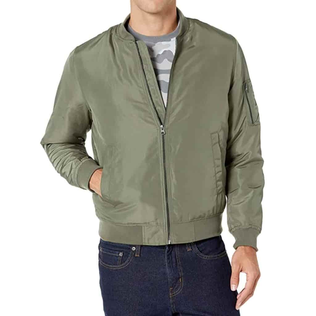 Person wearing dark blue jeans and an olive green bomber jacket.
