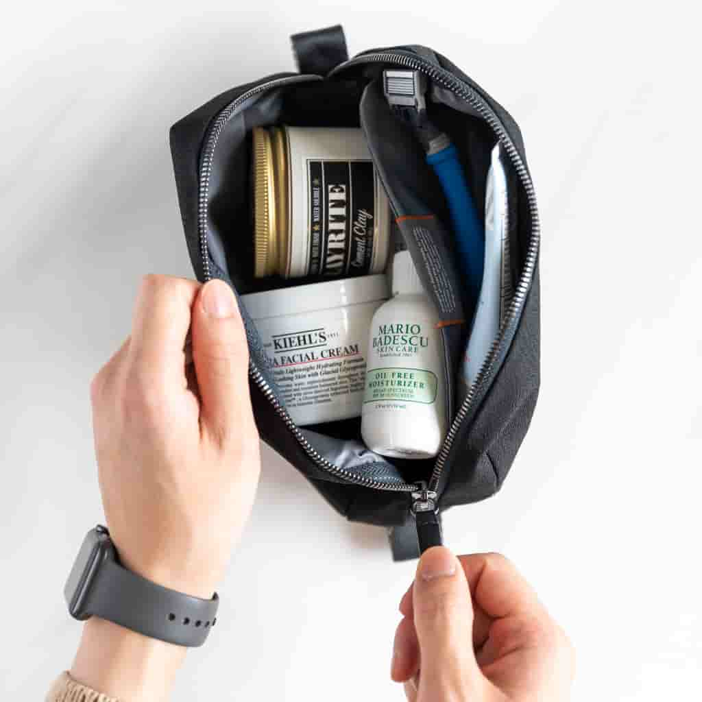 Hands opening a dopp kit with skincare products inside.