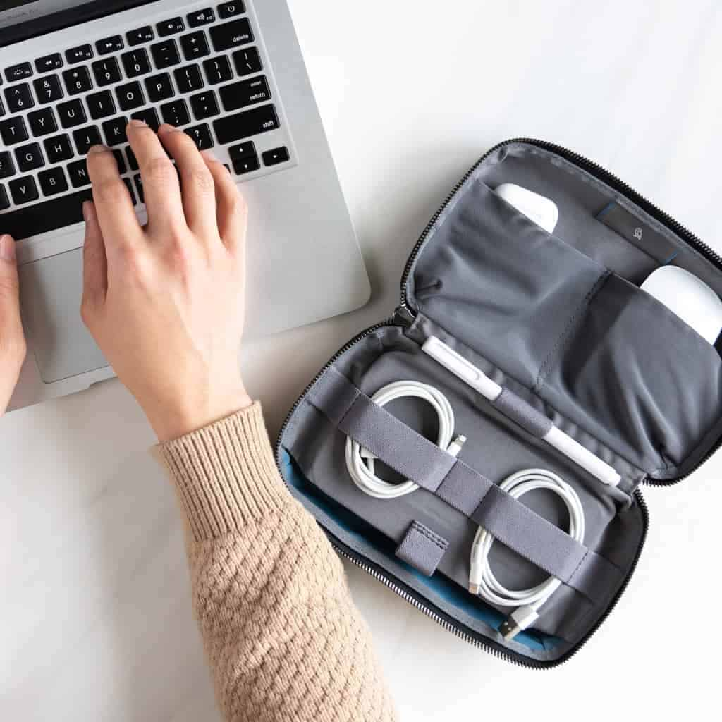 Tech kit organizer next to a person typing on their laptop.