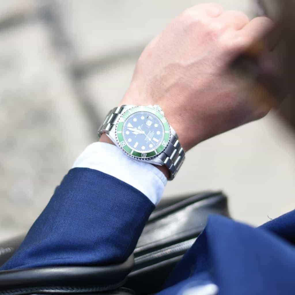 Person wearing a suit and looking down at their Rolex watch.