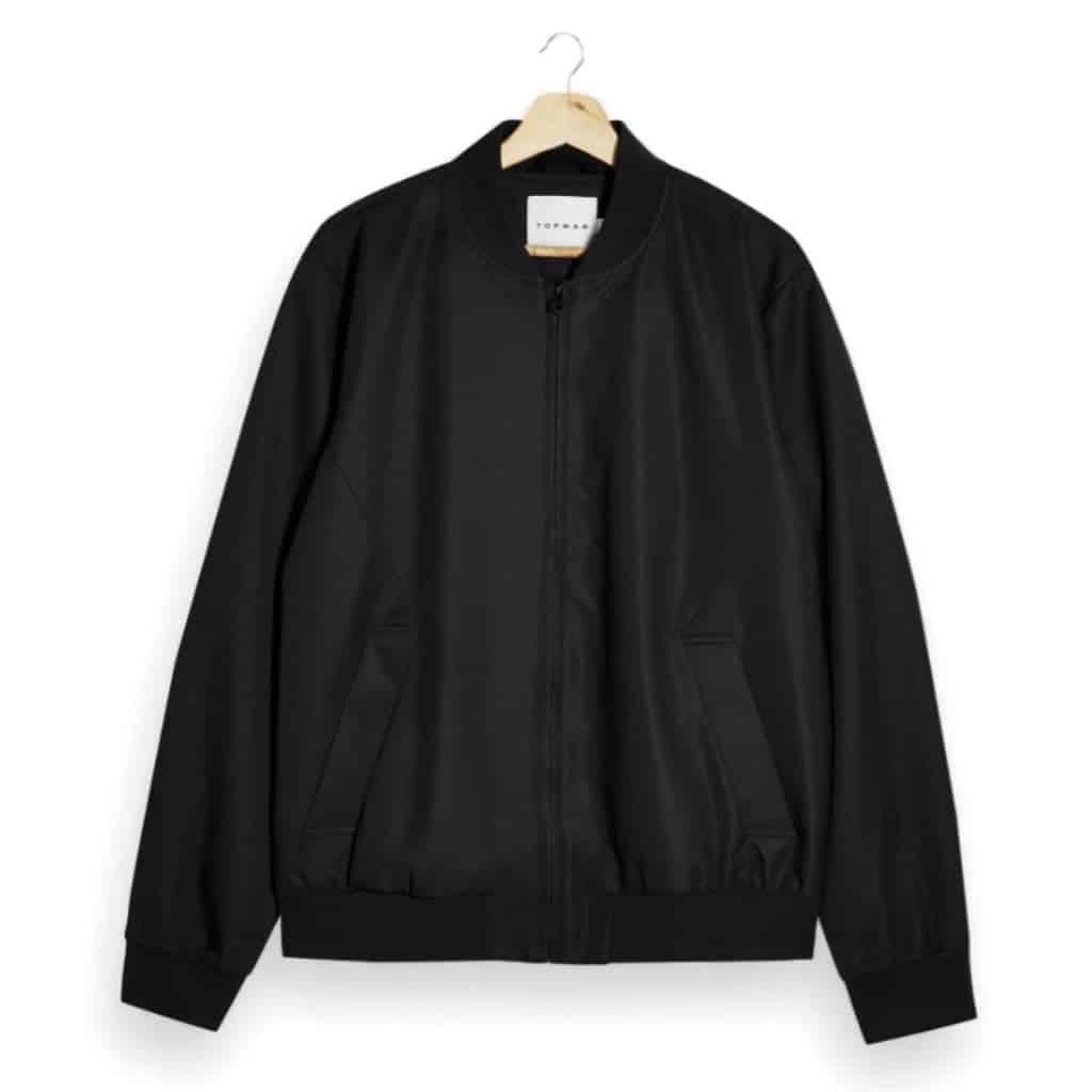 Black Topman bomber jacket on a wooden hanger.